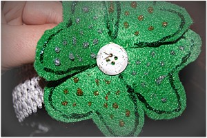 Sewing the clover to the headband using a button and a second piece of felt